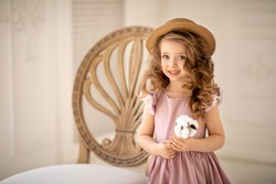 Portrait of a little girl in the studio. A girl standing near a chair. A girl in a pink dress and with blond curly hair. A Girl in a straw hat.  Image with selective focus.
