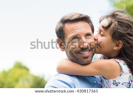 Portrait of a little girl kissing her dad on cheek. Pretty girl giving a kiss to her father outdoor. Loving child embrace and kissing her father.