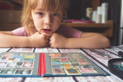 portrait of a little girl looking postage stamps on the table