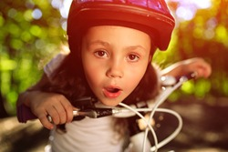 Portrait of a little girl on a bicycle in summer park against sunset