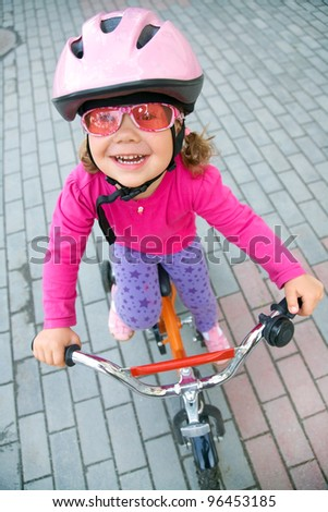 Portrait of a little girl on a bicycle in summer park outdoors
