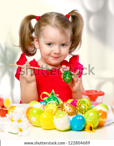 portrait of a little girl paints the eggs on a white background - stock photo
