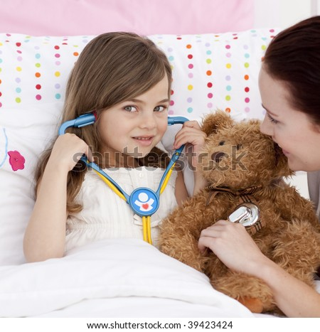 Portrait of a little girl playing with a stethoscope with her mother
