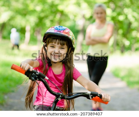 Portrait of a little girl riding her bike ahead of her mother #207389407
