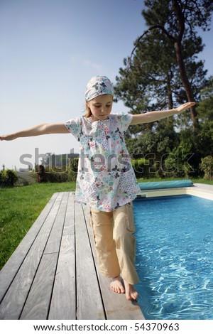 Portrait of a little girl walking beside a pool