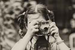 Portrait of a little girl with camera/ vintage/ sepia,/old photo/filter