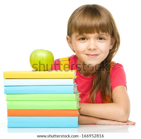 Portrait of a little girl with her books and green apple, isolated over white