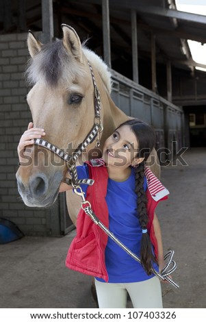Portrait of a little girl with her favorite horse in the stable
