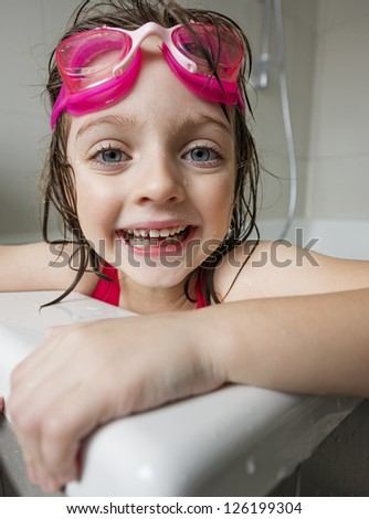 portrait of a  little girl with swim glasses in a bath - stock photo