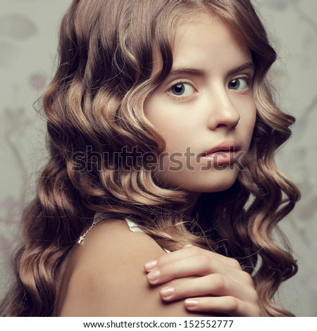 Portrait of a little princess posing over vintage background. Girl with perfect glossy long hair touching her shoulder. Retro & Vogue style. Close up. Studio shot