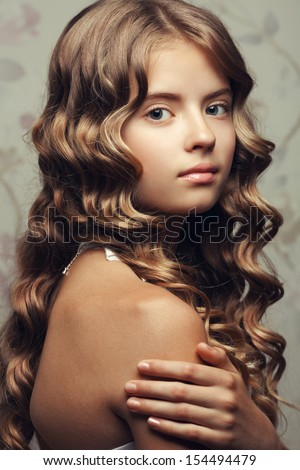 Portrait of a little princess smiling and posing over vintage background. Girl with perfect glossy long hair touching her shoulder. Retro & Vogue style. Close up. Studio shot