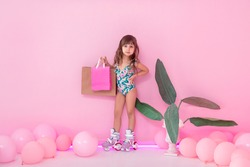 Portrait of a little roller-girl. Shopping, summer, vacation and travel concept. Baby girl in swimwear near pink background.