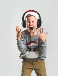 Portrait of a little Santa Clause boy in headphones. Emotional singing loudly while listening to music. Child shout Christmas songs at home. New Year