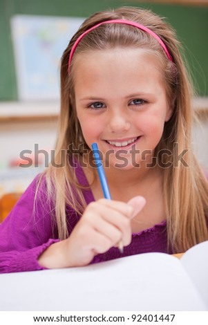 Portrait of a little schoolgirl writing on a book in a classroom