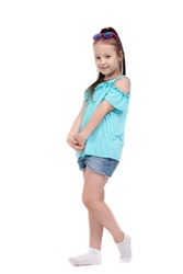 portrait of a little seven-year-old girl in full-length green t-shirt and shorts . little girl posing on white background
