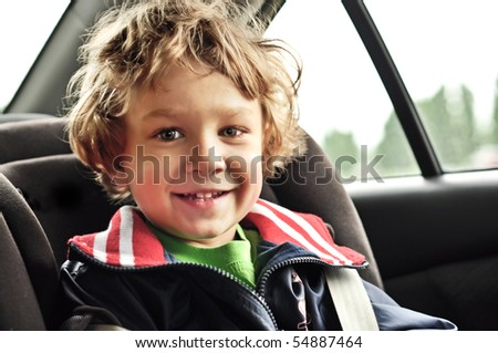 Portrait of a little smiling blond boy in the car