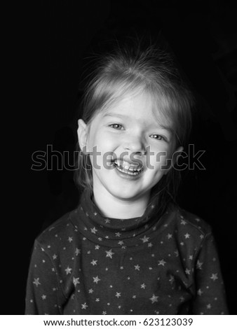 Portrait of a little smiling girl on a dark background #623123039
