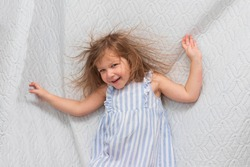 Portrait of a little smiling girl with electrified hair on a white background. Electricity power concept.