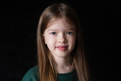 portrait of a little smiling girl with long blonde hair on black dark background