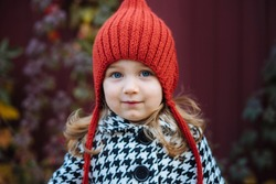 Portrait of a little toddler girl in red knitted hat standing in autumn scenery