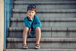 Portrait of a little unhappy boy on the porch