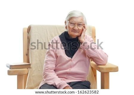 Portrait of a lonely elderly woman sitting in a fotel Zdjęcia stock ©