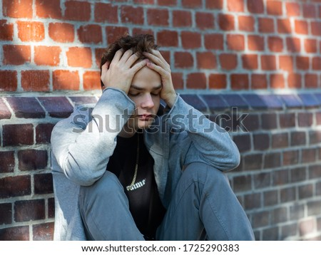 portrait of a lonely sad teenager in a hoodie with a hood on the street, problems and psychology of adolescents, concept. Young man holding his head Photo stock ©