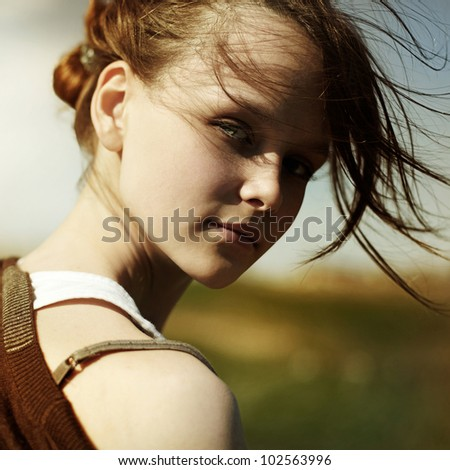 Portrait of a long-haired brunette with flying hair, the sun, summer, nature