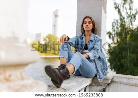 Portrait of a longing pensive teenage girl dressed in denim and boots, sitting, looking at camera. Horizontal view.