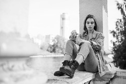 Portrait of a longing pensive teenage girl wearing in denim and boots, sitting, looking at camera. Horizontal view.