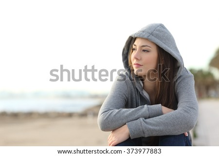 Portrait of a longing pensive teenager sitting on the beach looking away at the horizon in the morning