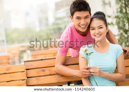 Portrait of a lovely couple on their first date, girl holding a white rose