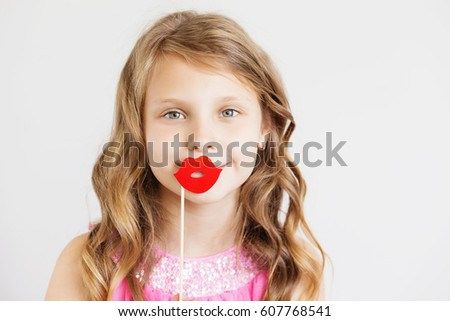 Portrait of a lovely little girl with funny red paper lips against a white background