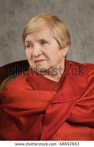 Portrait of a lovely old woman in a red