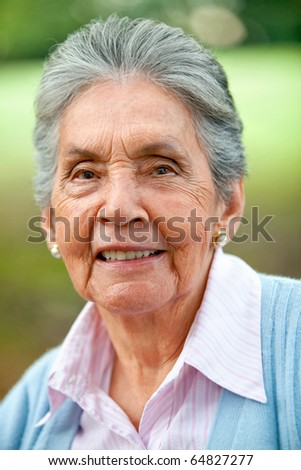 Portrait of a lovely old woman smiling outdoors - stock photo