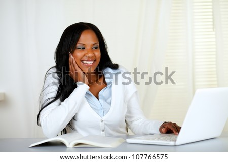 Portrait of a lovely relaxed student woman smiling and looking to a laptop at home indoor