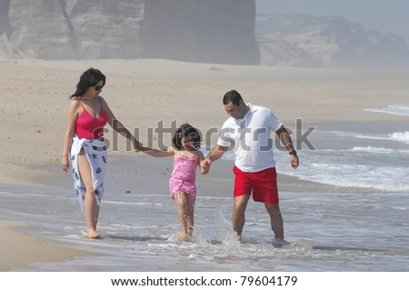 Portrait of a lovely romantic family on the beach - stock photo