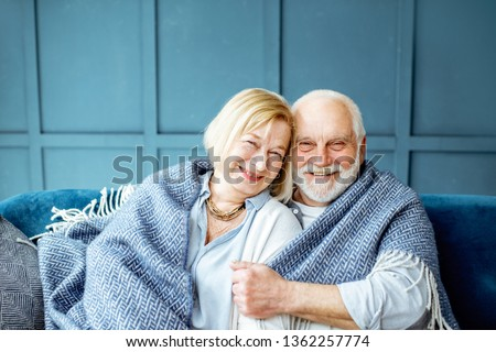 Portrait of a lovely senior couple feeling cozy and warm, sitting wrapped with plaid on the couch at home