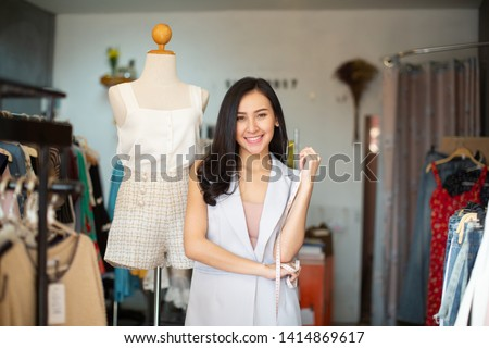 Portrait of a lovely shop owner standing near the rack of clothes hangings on the foreground