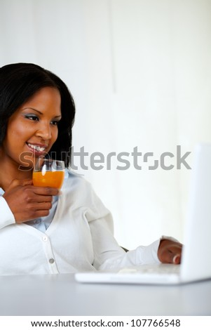 Portrait of a lovely student girl smiling and looking to laptop screen while drinking a healthy orange juice at soft colors composition