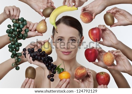 portrait of a lovely woman among lot of hands holding fruit