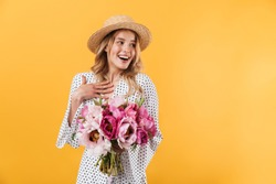 Portrait of a lovely young blonde girl wearing summer dress standing isolated over yellow background, holding peonies bouquet