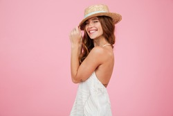 Portrait of a lovely young lady in summer dress and hat posing while standing and laughing isolated over pink background