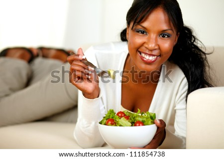 Portrait of a lovely young lady lying on a sofa and eating a vegetable salad while looking at you