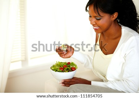 Portrait of a lovely young woman smiling and looking to a vegetable salad. With copyspace.