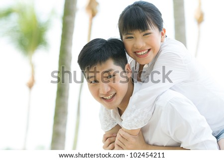 Portrait of a loving Asian couple enjoying themselves on holiday.