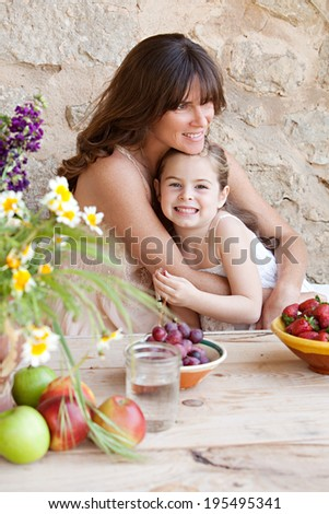 Portrait of a loving mother and young daughter sitting together at a holiday home table outdoors eating fresh fruits and enjoying a summer vacation, hugging. Family fun and healthy eating.