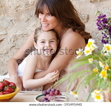 Portrait of a loving mother and young daughter sitting together at a holiday home table outdoors eating fresh fruits and enjoying a summer vacation, hugging. Family fun, travel and lifestyle.