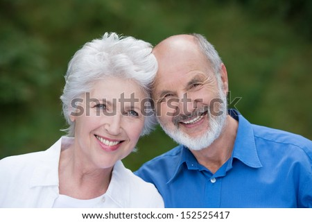 Portrait of a loving senior couple standing together outdoors facing the camera and smiling with their heads touching
