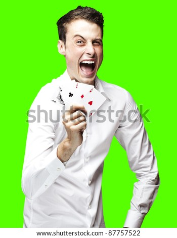 portrait of a lucky young man showing poker cards over a removable chroma key background